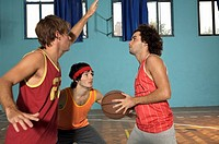 Three young men playing basketball