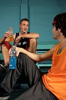 Two young men looking at each other and holding sport drinks (thumbnail)