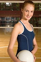Portrait of a young woman holding a volleyball and smiling (thumbnail)
