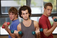 Portrait of three young men exercising with dumbbells