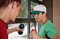 Two young men exercising with dumbbells in a gym (thumbnail)