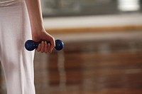 Mid section view of a woman holding a dumbbell