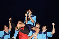 Soccer team cheering with their winning trophy
