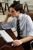 Side profile of a businessman sitting at a desk and working on a computer
