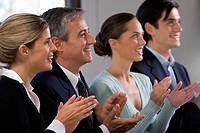 Side profile of four business executives clapping in a row and smiling