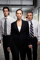 Portrait of a businesswoman walking with two businessmen