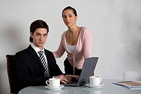 Portrait of a businessman working on a laptop with a businesswoman standing beside him