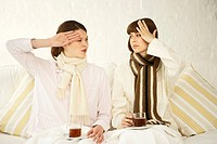 Two mid adult women holding cups of herbal tea and suffering from fever (thumbnail)