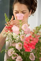 Mid adult woman sneezing behind a bouquet of flowers