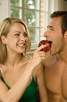 Close-up of a young woman feeding an apple to a young man