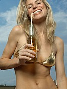 Portrait of a young woman drinking beer with a drinking straw and smiling