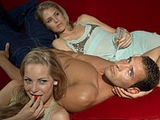 Portrait of a young man lying on a couch with two young women