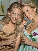 Close-up of two young women holding champagne flutes and smiling