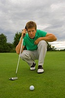 Portrait of a mid adult man crouching on a golf course (thumbnail)