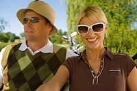 Close-up of a mid adult couple sitting in a golf cart and smiling