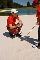 Side profile of a mid adult man giving golf training to his son (thumbnail)