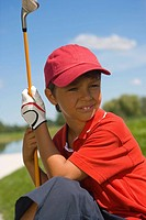 Close-up of a boy sitting on grass and holding a golf club
