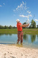 Side profile of a mid adult man swinging a golf club in waterhole in a golf course (thumbnail)
