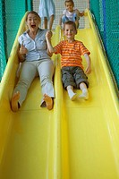 Portrait of a boy with a mid adult woman sliding on a slide