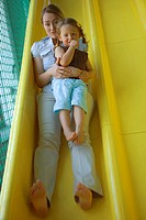 Portrait of a mid adult woman with a girl sliding on a slide
