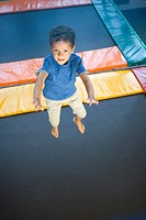 High angle view of a boy jumping on a trampoline