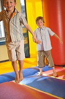 Two boys jumping on an inflatable bouncy castle