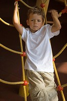 Boy standing on a rope climbing net