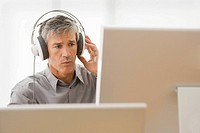 Businessman sitting in front of a desktop PC and listening to music