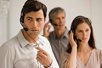 Three business executives wearing headsets