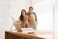 Two businesswomen and a businessman discussing in an office (thumbnail)