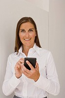 Portrait of a mid adult woman using a personal data assistant and smiling