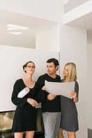 Businessman and a businesswoman holding a blueprint with another businesswoman standing beside them