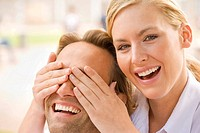 Portrait of a young woman covering a young man's eyes and smiling