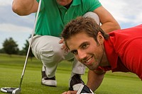 Close-up of two mid adult men playing golf in a golf course and smiling