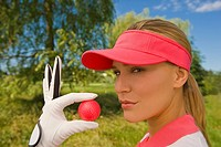 Portrait of a mid adult woman holding a golf ball