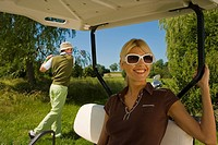 Mid adult woman sitting in a golf cart with a mid adult man playing golf in the background