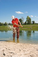 Mid adult man swinging a golf club in waterhole on a golf course