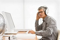 Portrait of a businessman working on a computer and listening to music