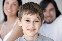 Boy 7-8 and parents smiling, portrait