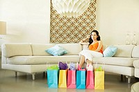 Woman relaxing at home with shopping bags, portrait