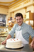 Young man in bakery, standing behind cake, smiling, portrait