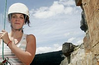 Portrait of teenage girl 16-17 rock climbing, wearing hardhat and harness, holding rope, smiling
