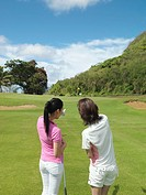 Women standing in golf course, rear view