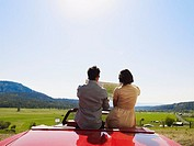 Couple sitting in convertible overlooking valley looking at map