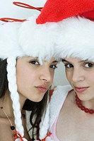 Two young female friends dressed in Christmas costumes, looking at camera, portrait