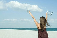 Woman standing on beach, rear view, holding up clear container, catching clouds, optical illusion