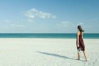 Woman walking across beach, carrying transparent container, full length, rear view (thumbnail)