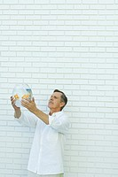 Man holding up goldfish bowl, standing in front of white brick wall, waist up