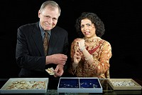Man holding money and woman trying on jewellery