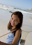 Girl 6-7with shells in net on beach, portrait